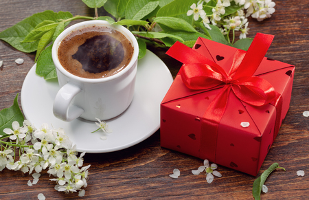 Surprise in red box and coffee in white cup, cherry twigs for girlfriend.