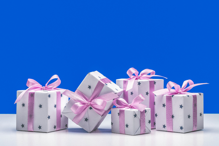 Stylish boxes with gifts in white paper in stars, decorated with pink satin ribbon with bows. Copy space. Фото со стока