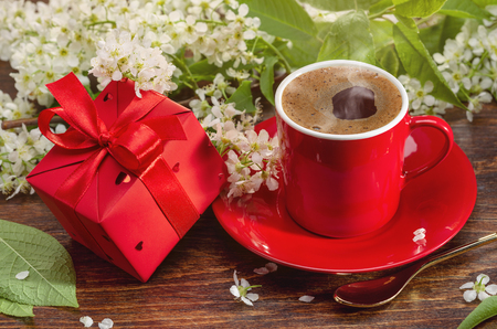 Morning coffee for the loved ones. Gift in red box and spring flowers. Фото со стока