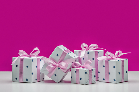 Boxes with gifts on pink background. Stylish modern gifts in white paper with asterisks, decorated with pink satin ribbon with bows. Holiday concept, copy space.