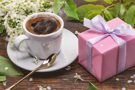 Wonderful spring breakfast. Fresh coffee in white cup, flowers and gift in pink box. Фото со стока