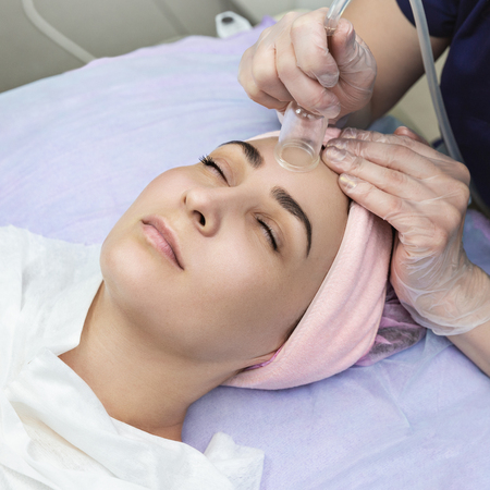 Doctor-cosmetologist makes procedure vacuum face cleaning of beautiful, young woman in beauty salon.Cosmetology and professional skin care.