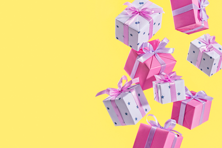 Flying gift box on yellow background. Concept of holiday, gift, sale. Birthday. Copy space. Фото со стока