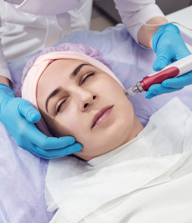 Pleasant relaxation. Beautiful young woman closing her eyes while having rejuvenation procedure. Face Skin Care. Фото со стока