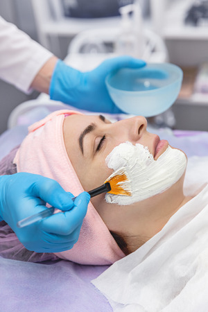 Spa therapy for young woman receiving facial mask at beauty salon. Face Skin Care.