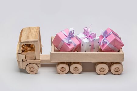 Truck with gifts in different boxes. Wooden toy car. Gray background, copy space, holiday concept. Imagens