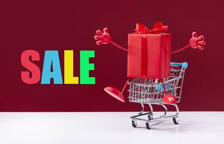 Decorative red gift box with ribbon in shopping cart. Discounts, sale, promotions. Stock fotó