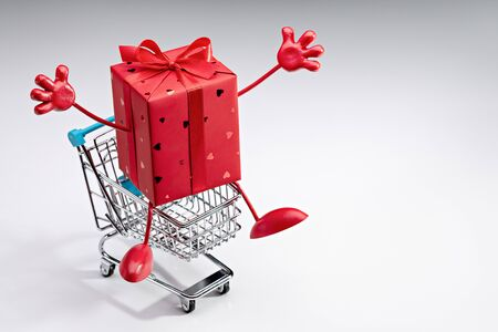 I am your gift! Shopping cart with surprise in red festive box with legs and hands.