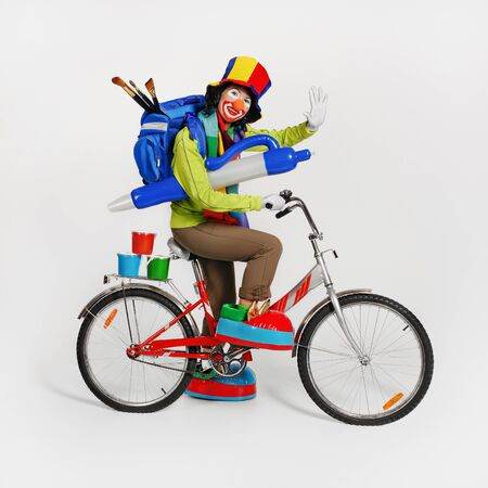 Female clown with backpack on her back, with paints and brushes, rides bicycle. A painted face, hat and big shoes. Studio shot.