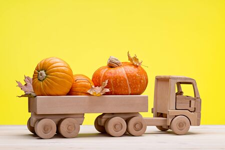 Orange pumpkins and dry maple leaves in wooden toy truck. Wooden background, yellow background, studio shot. Happy Halloween. Stock Photo