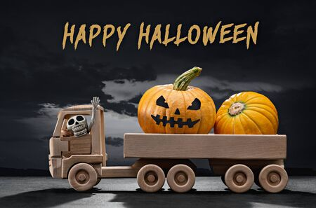Halloween. In wooden toy car, scary holiday pumpkins, in cabin skeleton of man. Gloomy black sky with clouds, shadows. Фото со стока