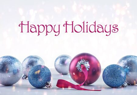 Happy Holidays. Multi-colored glass balls, decorations for winter holidays on bokeh background.