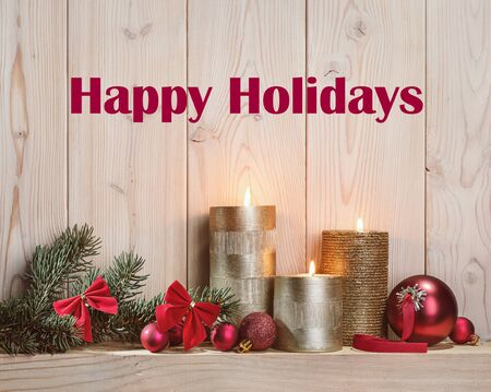 Happy Holidays. Burning golden candles, fir branches with red bows and glass red balls.