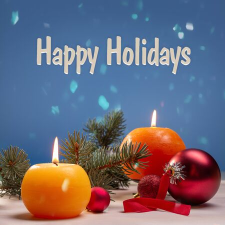Happy winter holidays. Burning round candles, green branches of spruce and glass red balls on a bokeh background.