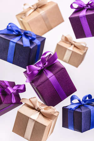 Gift. Flying boxes in colored paper tied with ribbon on white background, isolated.