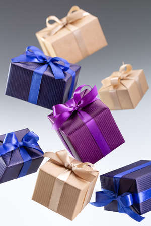 Present. Flying boxes in bright paper tied with ribbon with bow on gray background. Holidays and greeting card concept.