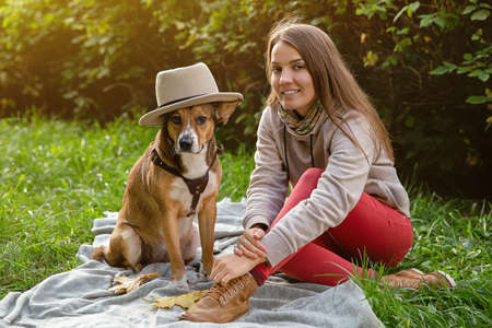 Autumn walk with your pet. A girl with dog in hat sitting on plaid. 版權商用圖片
