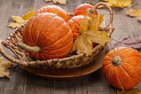 Orange round pumpkins in wicker basket on wooden background. Copy space, Halloween design.