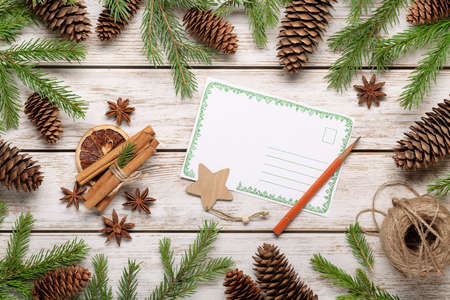Spruce branches and cones on light wooden background, accessories for winter holidays. Christmas card, congratulations, copy space. 版權商用圖片