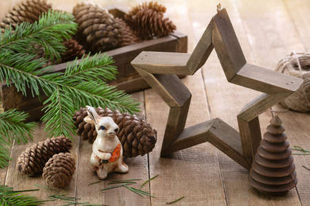 A large wooden star, rabbit, spruce branches and cones. Christmas card, winter holidays concept. 版權商用圖片