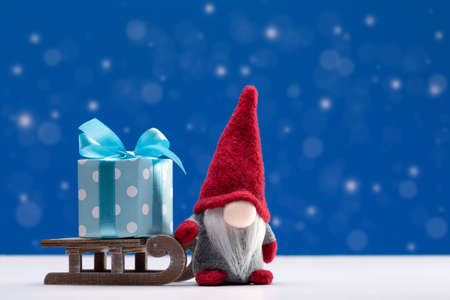 Christmas background. A gnome in red cap on sleigh carrying box of holiday gifts. Happy Holidays. 版權商用圖片