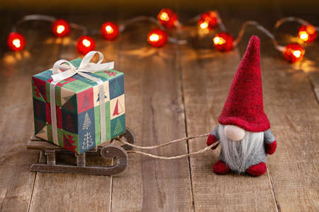 Christmas background. A gnome in red cap on sleigh carrying box of holiday gifts. Happy Holidays