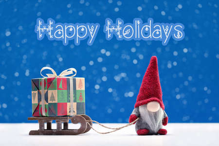 Happy Holidays. A gnome in red cap is on sleigh carrying box of holiday gifts. Winter background.