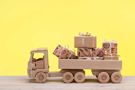 Truck with gifts in different boxes. Wooden toy car. Yellow background, copy space, holiday concept.