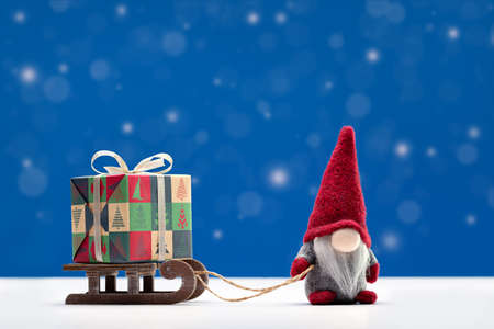 A gnome in red cap is on sleigh carrying box of holiday gifts. Winter background. Happy Holidays.