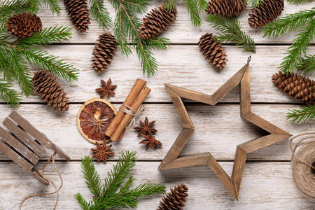 Spruce branches and cones on light wooden background, accessories for winter holidays. Christmas card, congratulations. 版權商用圖片