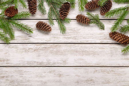 The concept of winter holidays and congratulations. Spruce branches and cones on light wooden background, copy space. 版權商用圖片