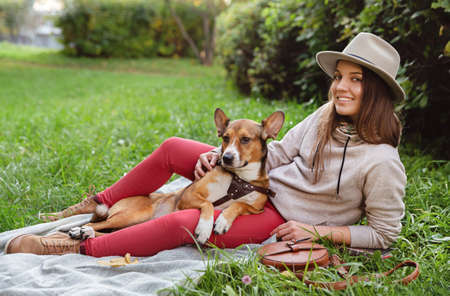 Smiling woman in hat with her dog sitting on plaid in an autumn park. 版權商用圖片