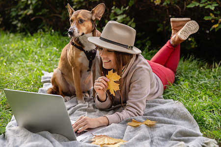 Smiling lady with laptop and dog  in the autumn park.