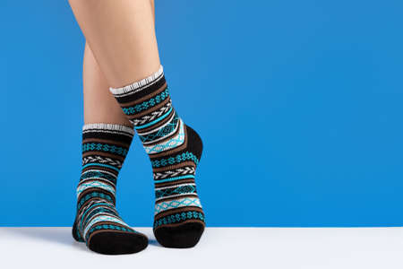 Female legs in cozy socks, blue background. Relaxation and comfort concept.