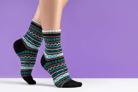 Female legs in cozy socks, lilac background. Unisex socks, close-up, studio shot.