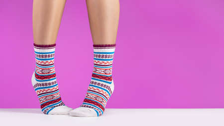 Close-up of colorful soft socks. Female legs comfort and relaxation concept, pink background.