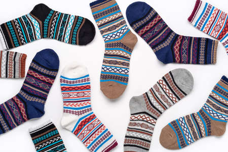 Concept background of colorful pile socks. Beautiful new unisex stretch sports socks isolated on white background. Close-up detailed studio shot.
