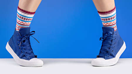 Female legs in blue sneakers and cozy socks, blue background. Relaxation and comfort concept. 版權商用圖片