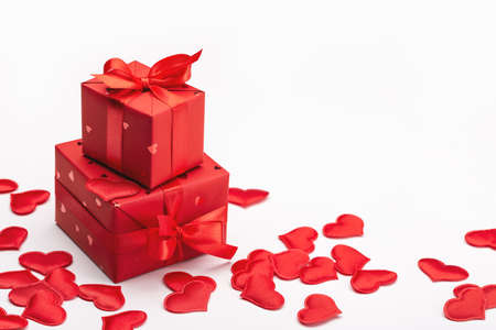 Gift box and red hearts on a light background, greeting card design.