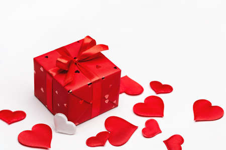 A gift for loved one in red box for Valentine's Day. Greeting card with hearts.