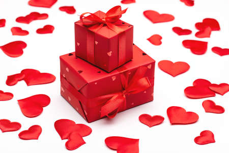 Beloved's gift for Valentine's Day. Box packed in red paper with red satin ribbon on light background.