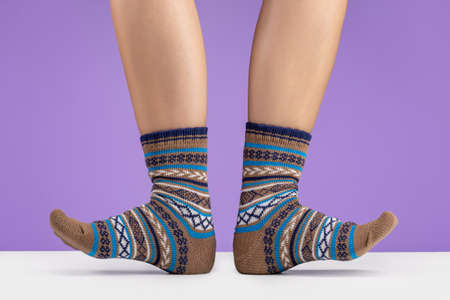 Warm knitted socks with an ornament on woman´s feet. Lilac background, studio shot.