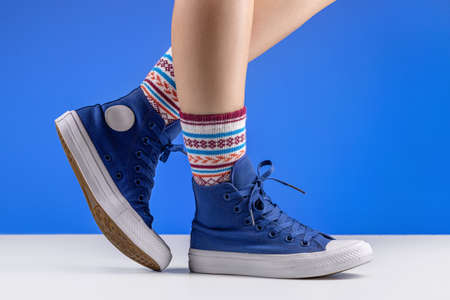 Female legs in blue sneakers and cozy socks, blue background. Relaxation and comfort concept. 版權商用圖片 - 158397499