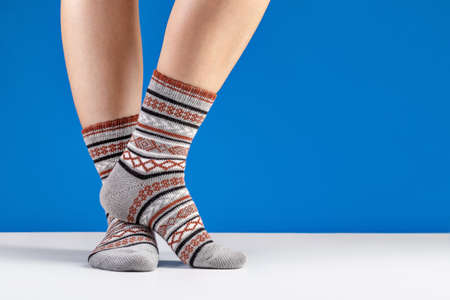 Women's feet in warm knitted socks with an ornament. Blue background, studio shot. 版權商用圖片 - 158366238