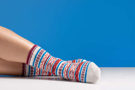 Close up of colorful soft socks on female legs. Space for design on blue background.