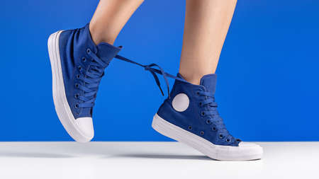 A pair of blue gym shoes, connected by laces, on women's legs. 版權商用圖片 - 158397504