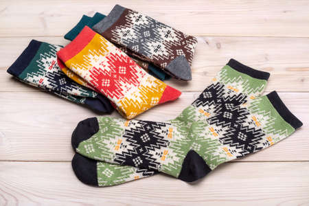 Colorful collection of elastic socks for sports and leisure. Wooden background, studio shot.