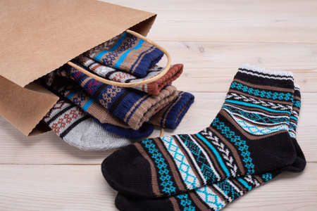 A paper bag with set of warm socks with an ornament. Wooden background, copy space.