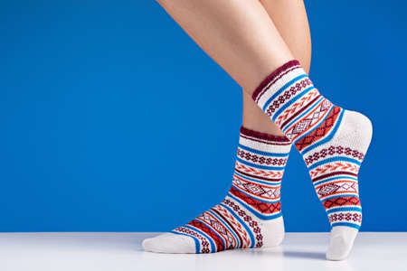 Close-up of colorful soft socks. Female legs comfort and relaxation concept, blue background. 版權商用圖片 - 158397673