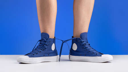A pair of blue gym shoes, connected by laces, on women's legs.
